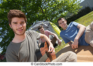 Young men sat outside a tent, playing guitar