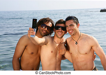 Young men taking pictures at the beach
