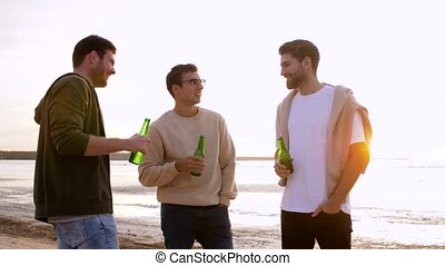 young men toasting non alcoholic beer on beach - friendship ...