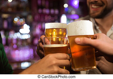 Young men toasting with beer while sitting in pub together -...