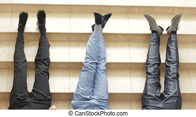 Young men wearing stylish shoes on stoned stairs background...