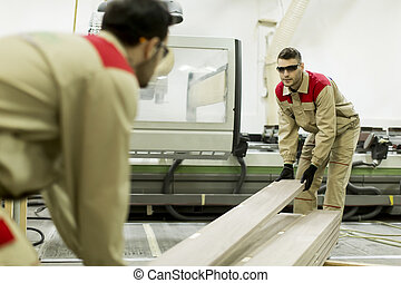 Young men working in furniture factory