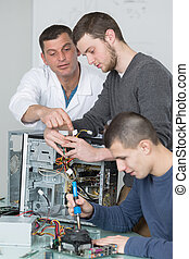 Young men working on dismantled computer