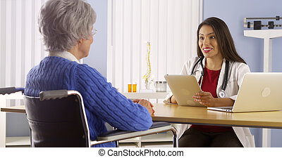 Young Mexican doctor talking with elderly patient