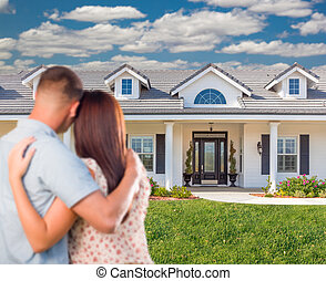 Young Military Couple Facing Beautiful New House.