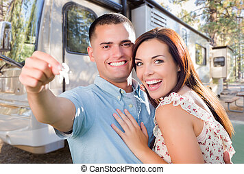 Young Military Couple Holding Keys In Front of New RV