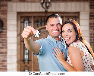 Young Military Couple In Front of Front Door of New House Holding Keys