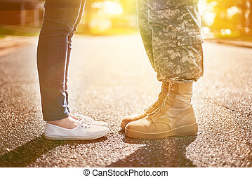 Young military couple kissing each other, homecoming concept, soft focus, warm orange toning applied