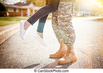 Young military couple kissing each other, homecoming...