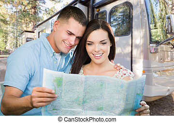 Young Military Couple Looking at Map In Front of RV