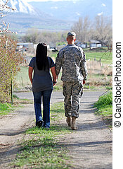 Young couple walking down a country lane holding hands. Young man in military uniform.