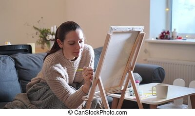 Young millennial woman painting with acrylic paints at home. Slow down hobby for lockdown. High quality FullHD footage