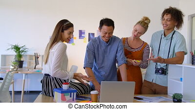 Young mixed-race business people working on laptop at desk in modern office and laughing together 4k