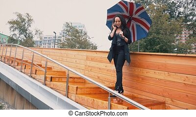 Young mixed race business woman talking on her mobile phone in the rain
