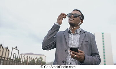 Young mixed race businessman listening to the music on his smartphone outdoors