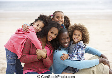 Young mixed race family embracing on beach