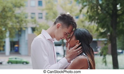Young mixed-race family of two touching foreheads and hugging outdoors
