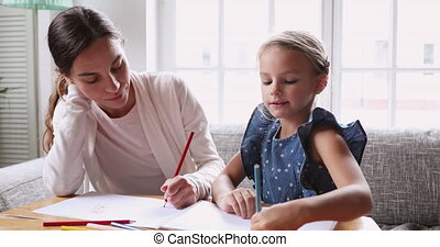 Young mixed race female tutor teaching little girl drawing...