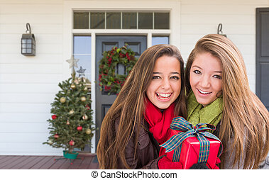 Young Mixed Race Girls Holding Wrapped Gift Standing on Christmas Decorated Front Porch
