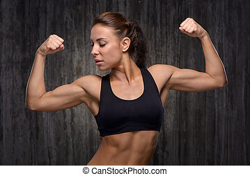 Young mixed race sporty woman demonstrating her biceps