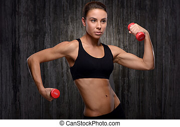 Young mixed race sporty woman holding dumbbells