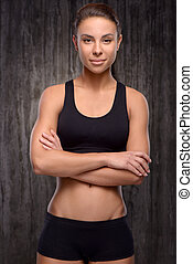 Young mixed race sporty woman looking at camera