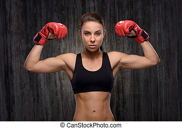 Young mixed race sporty woman wearing boxing gloves