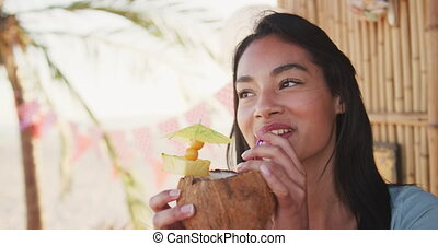 Young mixed race woman drinking cocktail - Close up of ...