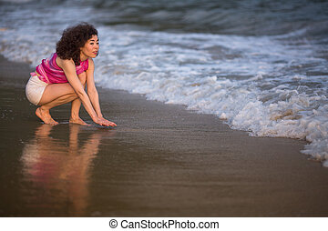 Young mixed race woman on a tropical beach.