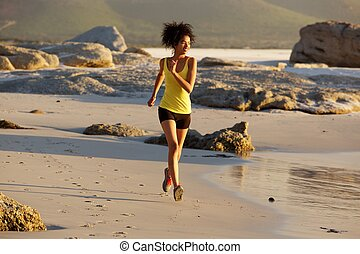 Young mixed race woman running on the beach