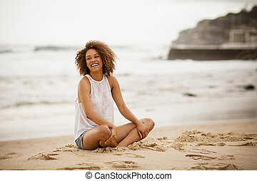 Young mixed-race woman stting on the beach