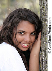 Young mixed teen girl outdoor portrait tree