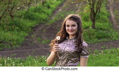 Young model blowing dandelion in the garden and smiling. Slowly