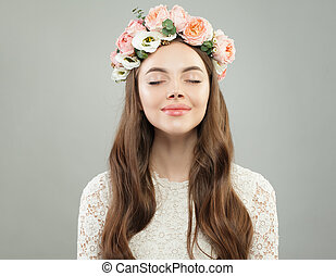 Young model face. Relaxing woman with clear skin and rose flowers portrait