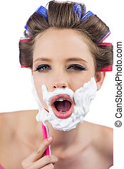Young model in hair curlers posing while shaving