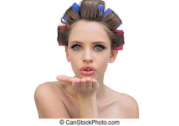 Young model in hair rollers blowing a kiss