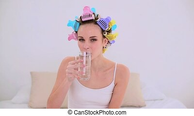 Young model in hair rollers drinking glass of water at home...