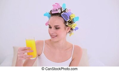 Young model in hair rollers drinking glass of orange juice...