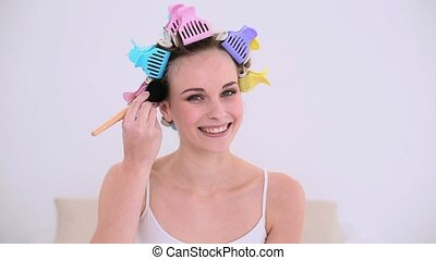 Young model in hair rollers putting make up on her face at...