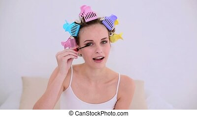 Young model in hair rollers putting on mascara at home in...