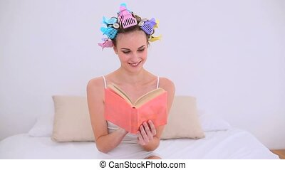 Young model in hair rollers reading a book on her bed at...