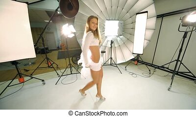 Young model walk inside photo studio, dances and blows kiss