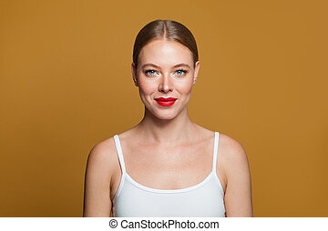 Young model woman smiling on yellow background
