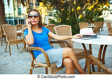 Young modern business woman talking on the phone in a cafe