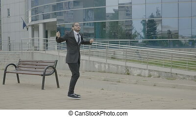 Young modern businessman in suit and tie leaving work and funny dancing joyfully on his way home