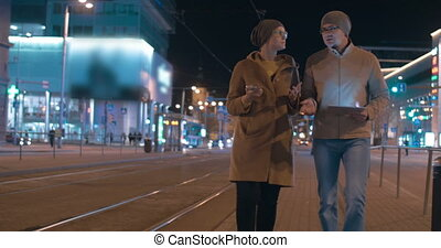 Young modern couple with tablet PC in evening city