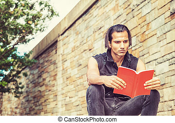 Young Modern East Indian American Man reading red book outside in New York City