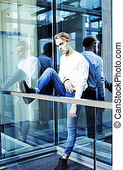 young modern hipster guy at new building university blond fashio