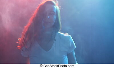 Young modern style dancer on a dark background with smoke and lights