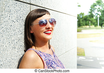 Young modern woman in sunglasses by the wall in city smiling.